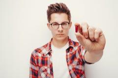 握一些药片手的红色衬衣的年轻严肃的人 库存照片