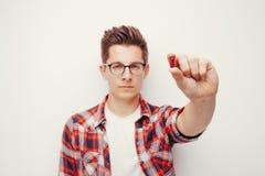 握一些药片手的红色衬衣的年轻严肃的人 图库摄影