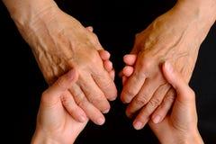握一名年长妇女的手的少妇的手 免版税库存图片