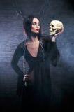握一块人力头骨的一个新深色的巫婆 库存图片