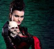 握一块人力头骨的吸血鬼夫人的纵向 免版税库存照片
