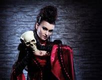 握一块人力头骨的吸血鬼夫人的纵向 库存照片