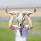 握一块白色角马头骨的妇女佩带它喜欢一个面具本质上在非洲野生生物徒步旅行队的 免版税库存照片