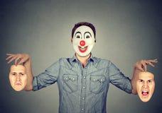 握两张面孔的愉快的小丑面具的人表现出愤怒和悲伤 免版税库存图片