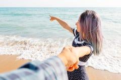 握人` s手和指向海上的妇女 库存照片