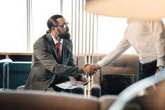 握他的商务伙伴的手的有胡子的富有的投资者 库存图片