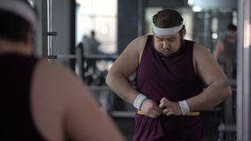 握他的有磁带的滑稽的肥胖人胃测量的腰部,看起来满意 股票视频
