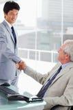 握他的经理的手的一位微笑的员工 免版税库存图片