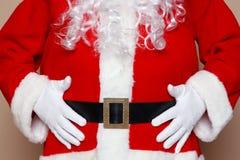 握他的腹部的圣诞老人 免版税库存照片