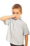 握他的鼻子的男孩 免版税库存图片