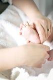 握儿童的一点脚的母亲 免版税库存照片