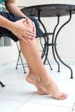握右膝用两只手的妇女,当坐下显示痛苦在膝盖时 免版税库存图片