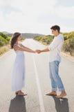 握在乡下路的爱恋的夫妇手 免版税库存照片