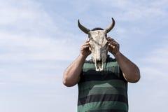 握在他的头前面的年轻人一块母牛头骨在b前面 免版税库存照片