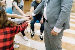 握在团结的学生顶视图手在轻的背景 黑色通信概念收货人电话 免版税库存照片