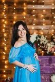 握在她胃和微笑的愉快的怀孕的深色的妇女手 免版税库存照片