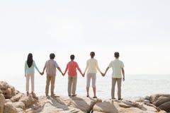 握在岩石的多代家庭手由海,背面图 库存图片