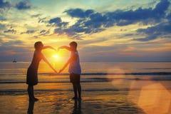 握在心脏形状的年轻夫妇剪影手在海洋海滩 免版税库存照片