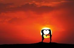 握在心脏形状的年轻运动的妇女手在日落 库存照片