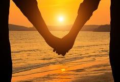 握在日落的剪影年轻夫妇手 库存照片