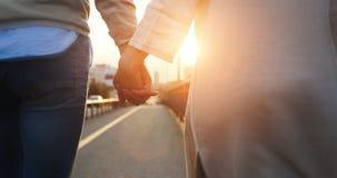 握在日落的愉快的夫妇手 库存图片