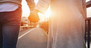 握在日落的愉快的夫妇手 免版税库存图片