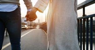 握在日落的愉快的夫妇手 免版税库存照片