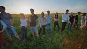 握在日落背景的十九个朋友剪影手 在行动的录影 股票录像