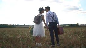 握在晴朗的领域的后面观点的愉快的新婚佳偶手 葡萄酒加工好的新娘拿着花束 股票录像