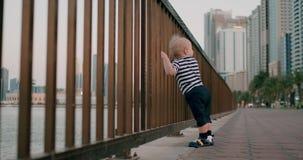 握在栏杆的婴孩逗人喜爱的跳舞手在江边在城市的背景中 股票录像