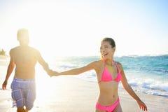 握在海滩妇女微笑的俏丽的夫妇手 免版税库存图片