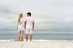 握在海洋岸的愉快的夫妇手在海滩 库存照片