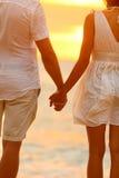 握在海滩日落的浪漫夫妇手 库存照片