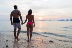 握在海滩的夫妇手在日落后面背面图、年轻旅游男人和妇女海假日 库存图片