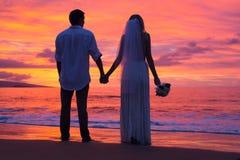 握在海滩的已婚夫妇手在日落 免版税图库摄影