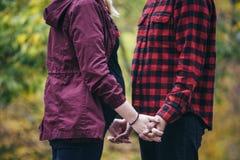 握在红色衬衣的怀孕的夫妇手 免版税库存照片