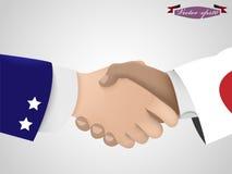 握在美国人和日本人之间的手 免版税图库摄影