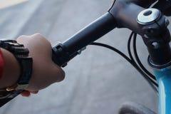 紧握在自行车的把手的手 库存照片