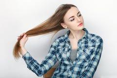 握在蓝色格子花呢上衣的年轻可爱的新鲜的看起来的白肤金发的妇女秀丽画象头发 情感和表情conce 免版税图库摄影