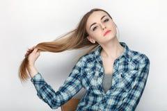 握在蓝色格子花呢上衣的年轻可爱的新鲜的看起来的白肤金发的妇女秀丽画象头发 情感和表情conce 免版税库存照片