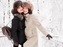 握在裘皮帽的可爱的愉快的年轻深色的妇女手有乐趣多雪的冬天公园森林本质上 图库摄影