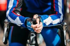 握在轮子路自行车把手的人手  免版税库存照片