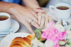 握在巴黎人咖啡馆的已婚夫妇手 图库摄影