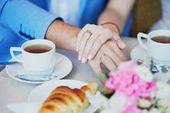 握在巴黎人咖啡馆的已婚夫妇手 免版税库存照片
