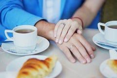 握在巴黎人咖啡馆的已婚夫妇手 库存照片