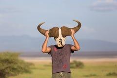 握大非洲水牛头骨的人佩带它喜欢一个面具本质上在非洲野生生物徒步旅行队的 库存图片