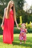 握女孩的手的草坪的桃红色礼服的妈妈 免版税库存照片