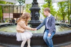 握女孩` s手的男孩 坐在喷泉的孩子室外 爱友谊乐趣概念 小成人 免版税库存照片