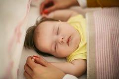 握她作的婴孩的手的母亲 免版税库存图片