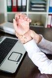 握她痛苦的腕子的女实业家 免版税库存照片